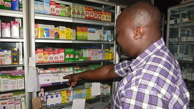 Ein Afrikaner in kariertem Hemd zeigt auf einen Schrank mit Medikamenten.
