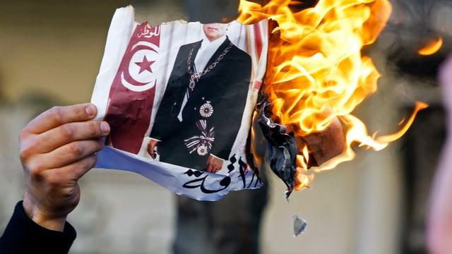 Proteste gegen den tunesischen Machthaber Ben Ali 2011 in Frankreich. Ein Mann hält ein brennendes Bild Ben Alis in der Hand.
