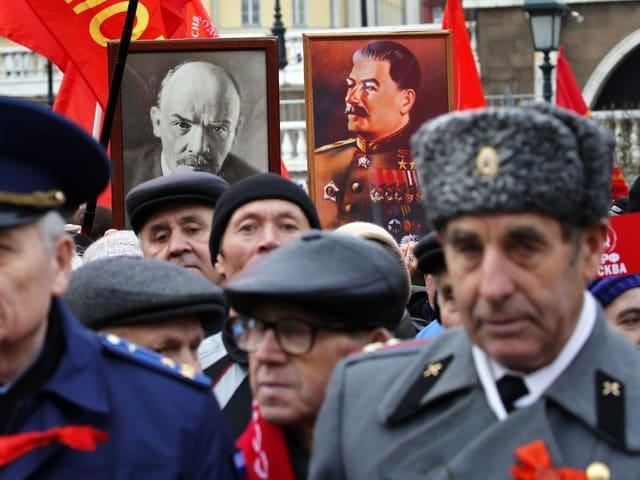 Kommunisten mit Bildern von Stalin und Lenin