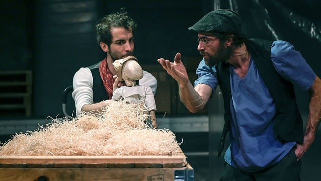 Zwei Männer auf einer Bühne: der eine hält eine Holzpuppe in den Händen.
