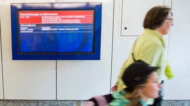 Grossmutter mit Enkelin geht an SBB-Störmelde-Bildschirm vorbei
