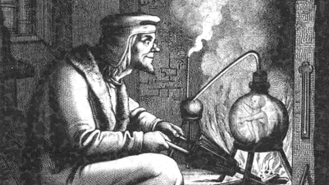 Ein Mann sitzt vor einem Reagenzglas, in dem ein Mensch zu erkennen ist.