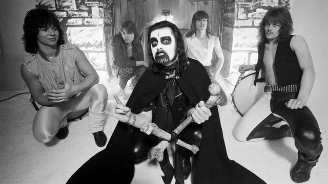 Ein schwarz-weiss geschminkter Mann mit fünf Band-Mitgliedern links und rechts von ihm.