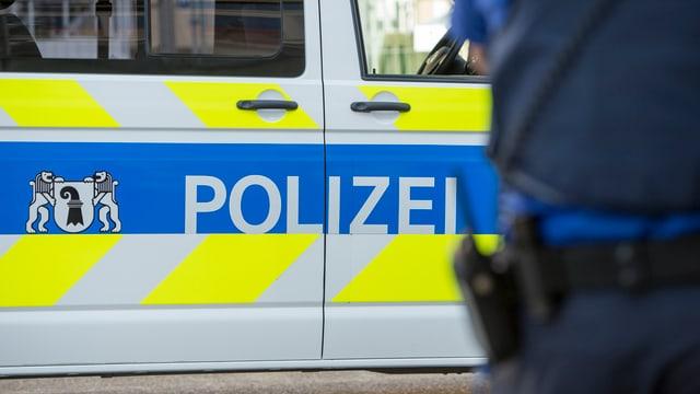 Polizei-Logo auf einem Einsatzwagen mit einem Polizisten im Vordergrund.