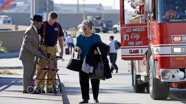 Feuerwehrmann hilft älterem Herrn mit Rollator