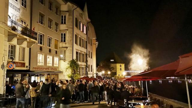 Ausgang in Solothurn. Menschen stehen vor einer Bar am Fluss.