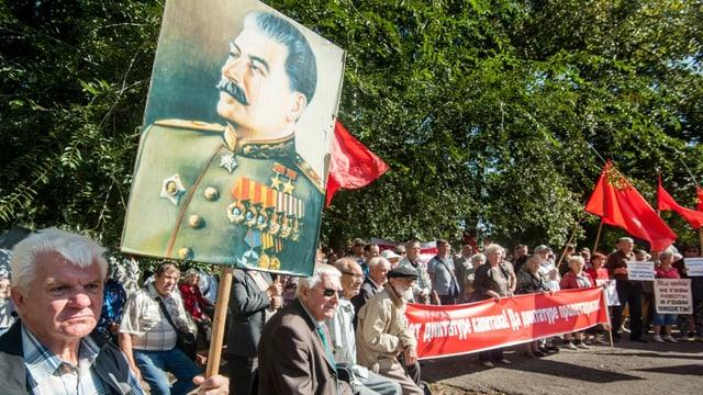 Demonstranten halten ein Plakat mit Stalins Konterfei in die Luft.