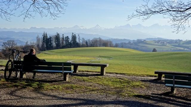 Ein Wanderer geniesst den Ausblick vom Gurten zu den aperen Berner Alpen.