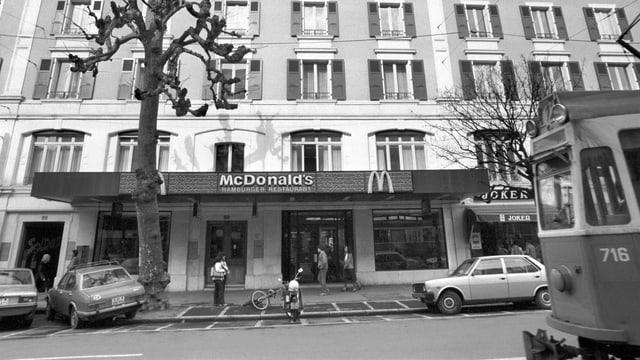 eine schwarz-weiss Aufnahme eines McDonalds in Genf, an der Strasse davor fährt ein Tram
