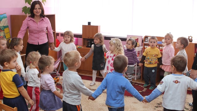 Eine Kindergartenklasse steht im Kreis.