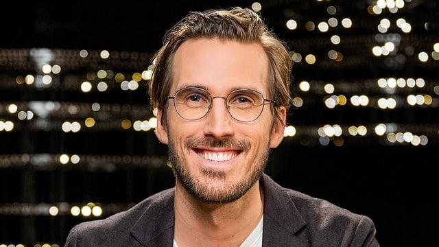 Ein Mann mit runder Brille grinst in die Kamera.