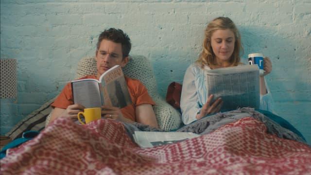 Ein Mann und eine Frau liegen im Bett, sie lesen beide.