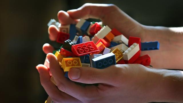 Eine Hand voll mit Lego-Steinen.