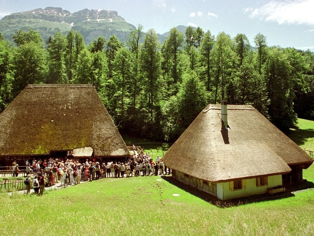 Zwei Häuser mit Rietdach und zahlreiche Leute, die zur Besichtigung schlangestehen.