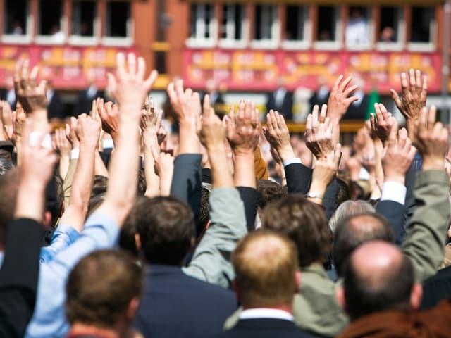 Leute stehen auf einem Platz und stimmen per Handheben ab.