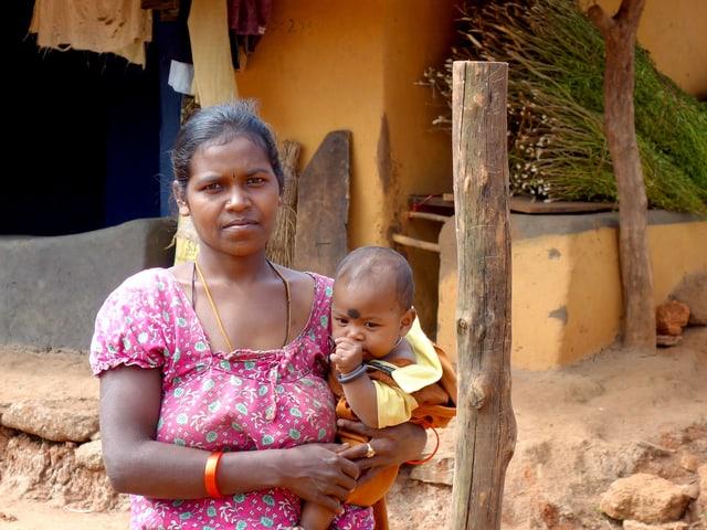 Eien Frau und ein Baby vor einer einfachen Hütte.