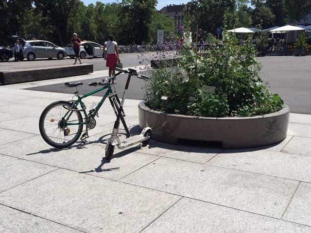 Ein E-Trottinett steht neben einem Fahrrad.