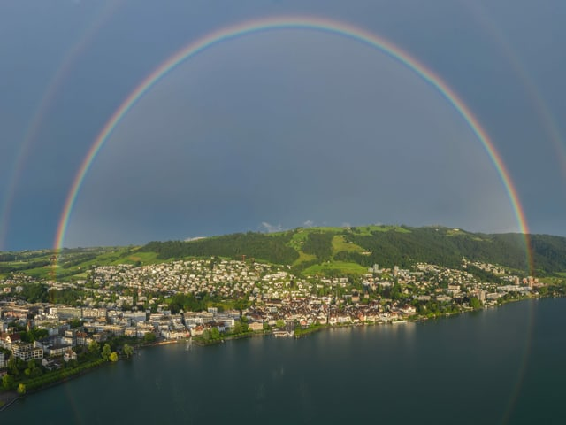Regenbogen über Landschaft mit See, Stadt am Ufer und grünem Berg