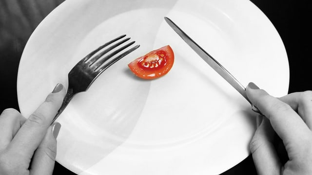 Eine einsame Tomate auf einem Teller, darüber Messer und Gabel in den Händen einer Frau.