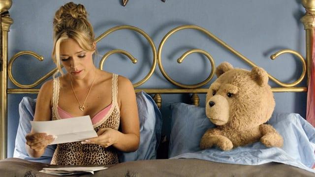 Eine Blondine liest im Bett einen Brief, ihr lebendiger Teddybär sitzt neben ihr und blickt sie besorgt an.