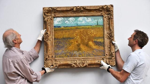 Im Museum: Zwei Männer hängen ein Bild von Vincent van Gogh an die Wand.