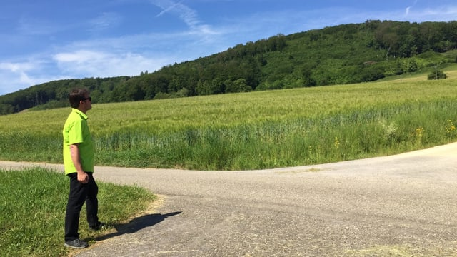 Mann in hellgrünem Hemd auf Feldweg.