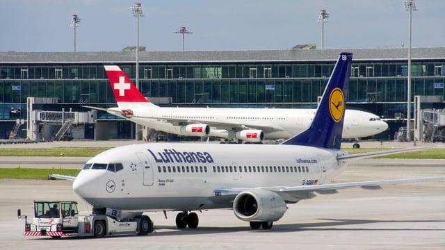 Ein Lufthansa- und ein Swiss-fFlugzeug stehen am Boden in Zürich-Kloten.