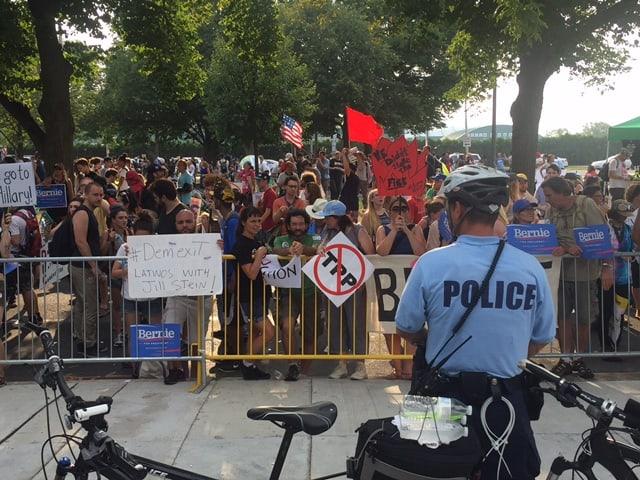 Wütende Demonstranten am Parteitag der Demokraten in Philadelphia vor einem Absperrgitter. Davor steht ein Polizist.