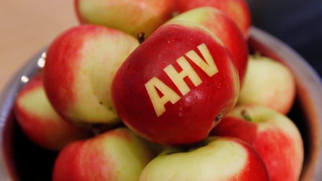 Äpfel liegen in einem Korb. Ein Apfel trägt das Wort AHV.