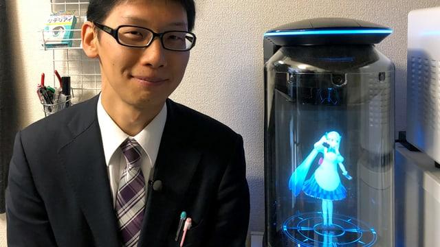Ein Mann steht neben einem Hologramm.