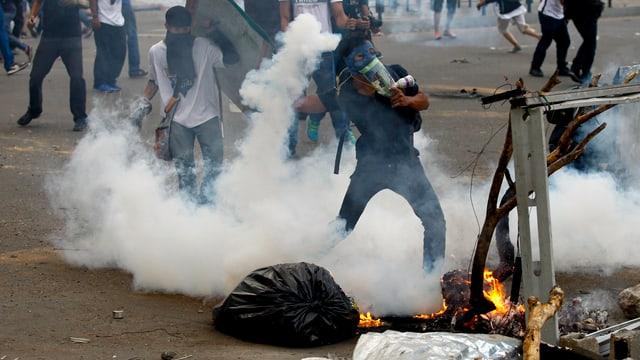 Vermummte Demonstranten in Venezuela. Einer wirft eine Rauchbombe.