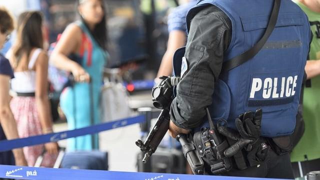 Purtret d'in policist ferm armà che stat davant ina porta per proteger.