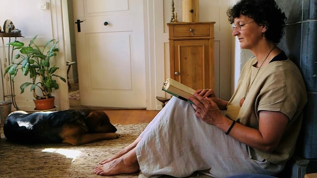 Eine Frau sitzt am Boden und liest ein Buch. Neben ihr liegt ein Hund.