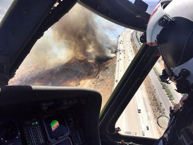 Blick aus einem Löschhelikopter, man sieht unten die Feuer und eine Autobahn.