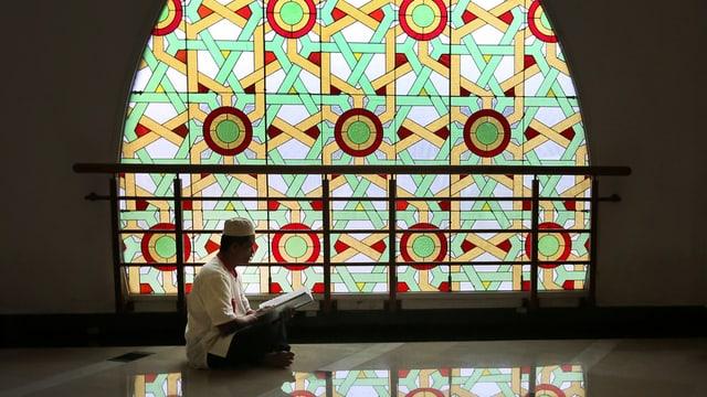 Mann mit weissem Hut und weissem Hemd sitzt vor farbigem Fenster