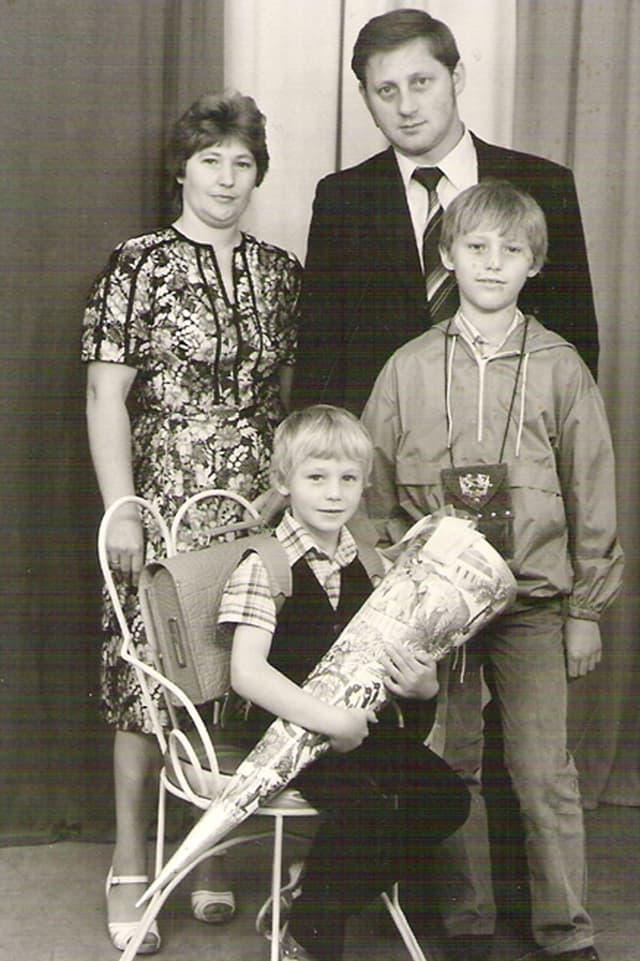 Christian Grothes Familie bei dessen Schuleinführung. Stehend Mutter, Vater, Bruder. Christian auf einem Stuhl sitzend mit einer Zuckertüte in der Hand.