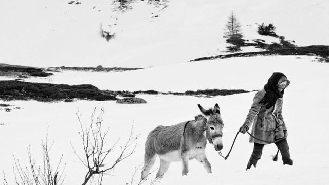 Eine karge Schneelandschaft; ein Mädchen mit dunkler Haut, dich eingepackt, stapft durch den Schnee. Sie führt einen Esel an einem Seil hinter sich her.