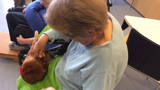 Eine Frau streichelt ein Huhn