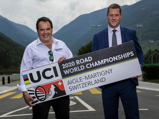 Alexandre Debons und Grégory Devaud vom OK der Heim-WM mit einem Banner, auf dem Aigle-Martigny steht