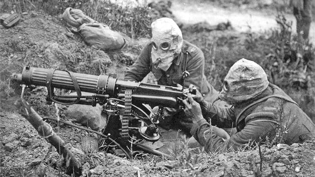 Zwei Soldaten mit Gasmasken liegen am Boden hinter einem Maschinengewehr.