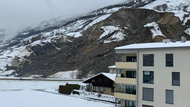 Bild des abgerutschten Hanges, im Vordergrund Wohnhäuser.
