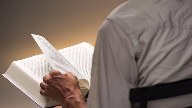Eine Hand blättert die Seite eines dicken Buches um.