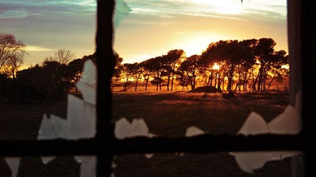 Blick durch ein zerbrochenes Fenster auf einen Sonnenuntergang in der argentinischen Pampa.