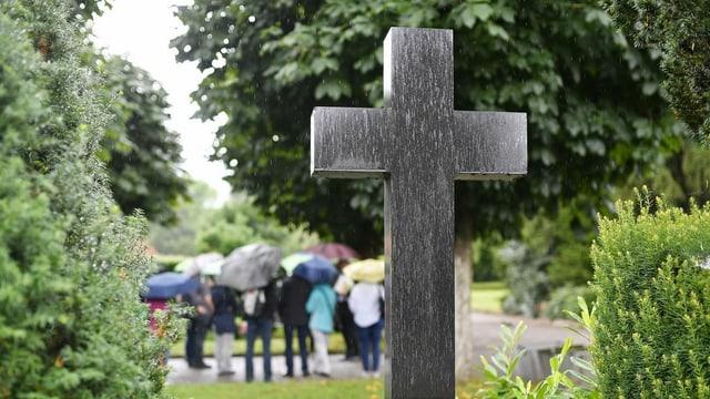 Leute mit Regenschirmen auf einem Friedhof, davor ein Kreuz.