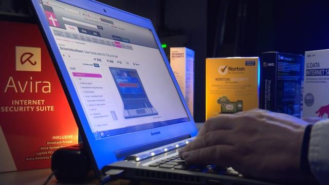 Ein Mann arbeitet an einem Laptop, darum herum stehen verschiedene Antivirenschutz-Programme.