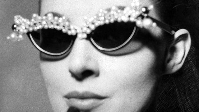 Eine Frau trägt eine schmetterlingsförmige Brille mit Perlen am oberen Rand.