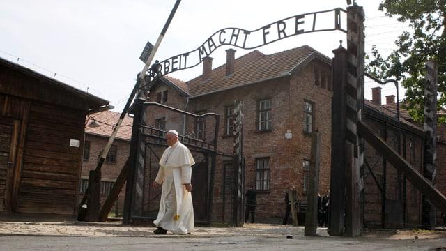 Papst Franziskus geht durch Auschwitz-eingangstor, über ihm steht Arbeit macht frei