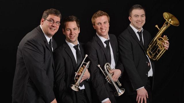 Vier Blasmusikanten in dunklen Anzügen.