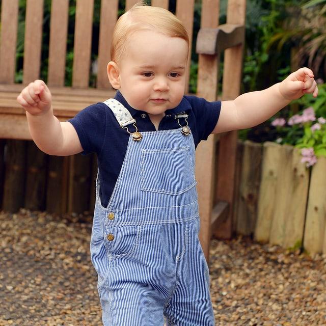 Prinz George in Latzhosen und erhoben Armen.