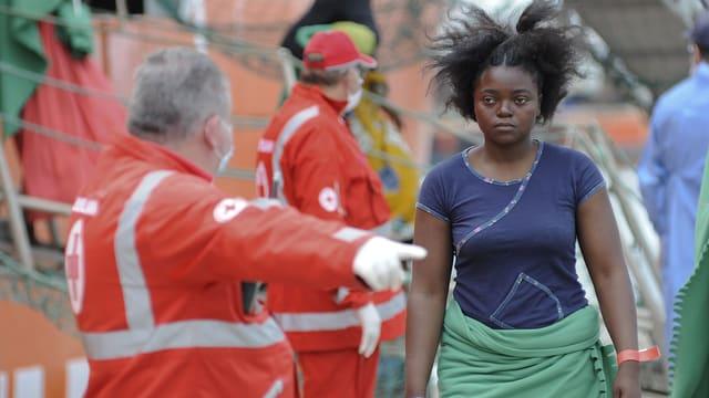 Ein Mitarbeiter des IKRK in rotem Anzug und mit Mundschutz weist einer jungen Afrikanerin einen Platz zu.